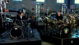 Neil Peart gives Rick Mercer a drum lesson